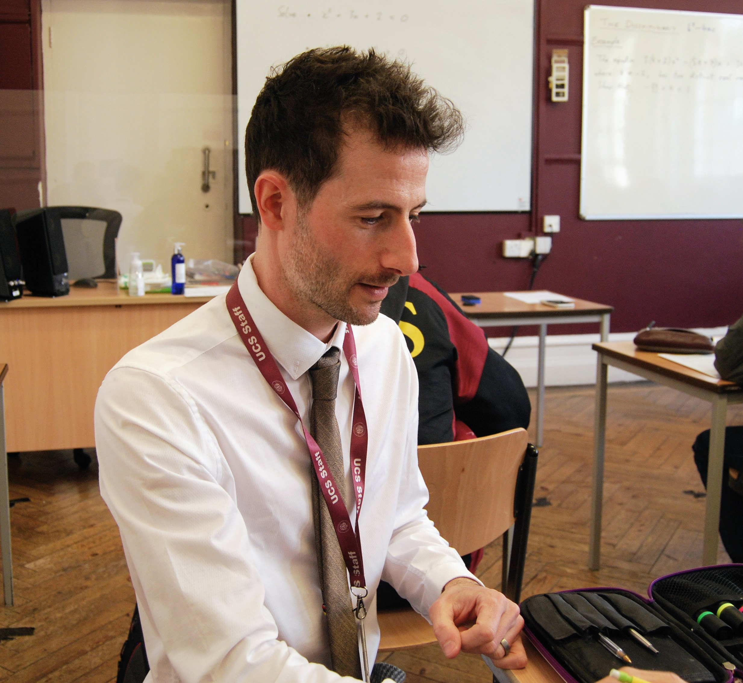 Micky Bullock teaching at a pupil's desk